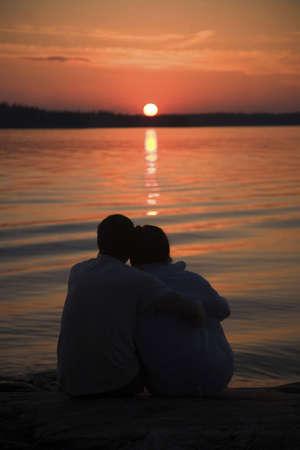 Romantic couple watching sunset at the beach Stock Photo - 3193456