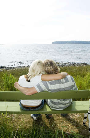 Couple sitting on the bench enjoying the seaview Stock Photo - 3193466