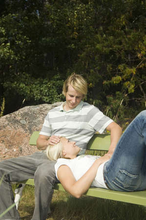 Man sitting on the bench with his girlfriend lying on his lap Stock Photo - 3193486