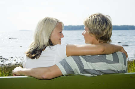 Couple looking at each other while sitting on the bench Stock Photo - 3193487