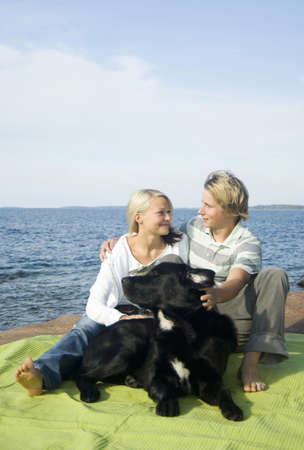 Couple with their dog picnicking by the seaside Stock Photo - 3193495