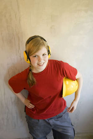 protectors: Teenage girl with ear protectors holding safety helmet