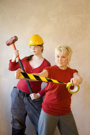 sledge hammer: Women posing with sledge hammer and adhesive tape