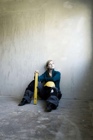 spirit level: Young woman with spirit level and safety helmet LANG_EVOIMAGES