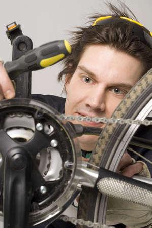 road bike: Man repairing his bicycle LANG_EVOIMAGES