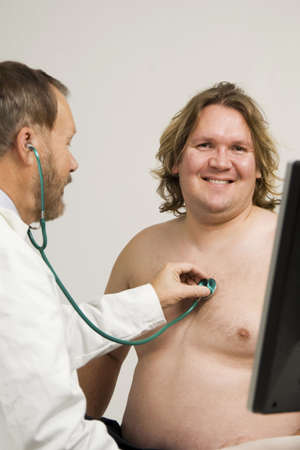 treating: Doctor giving patient a body check up LANG_EVOIMAGES