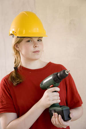 Teenage girl with safety helmet holding a drill Stock Photo - 3193554