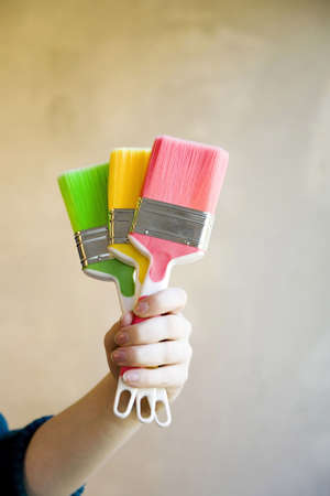 home decorating: Hand holding colourful paint brushes