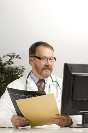 Doctor holding a patients x-ray film and looking at the laptop LANG_EVOIMAGES