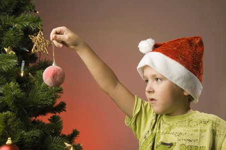 decorating christmas tree: Boy with santa hat holding Christmas ornament