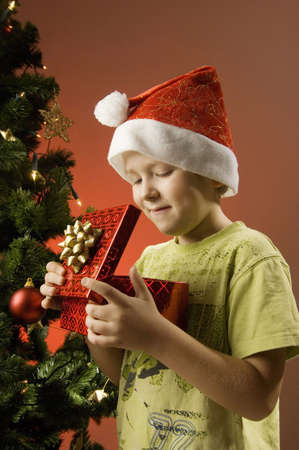 holding a christmas ornament: Boy with santa hat looking into a gift box