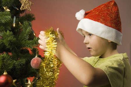 festoon: Boy decorating Christmas tree with festoon LANG_EVOIMAGES