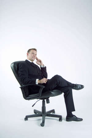 Businessman sitting on office chair, thinking