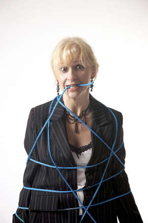 Tied up businesswoman biting on rope Stock Photo - 3193692