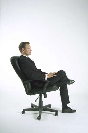 ofis koltuğu: Businessman sitting on office chair, side view