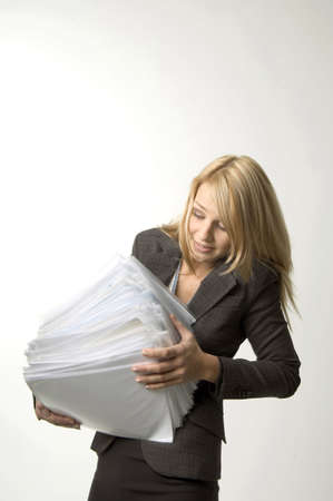 Businesswoman balancing a stack of paperwork LANG_EVOIMAGES