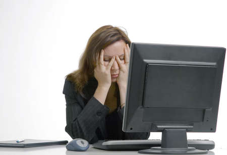 Businesswoman with hands covering her face, in front of desktop Stock Photo - 3193734