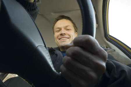 Man smiling at the camera while driving in the car Stock Photo - 3193782