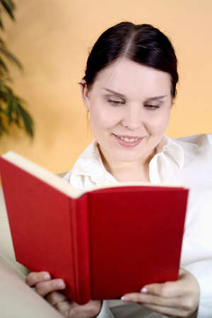 Woman smiling while reading Stock Photo - 3193802