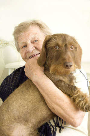 carrying: Senior woman posing with pet dog in her arms
