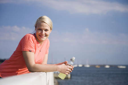 Woman with a bottle of drink smiling at the camera Stock Photo - 3193848