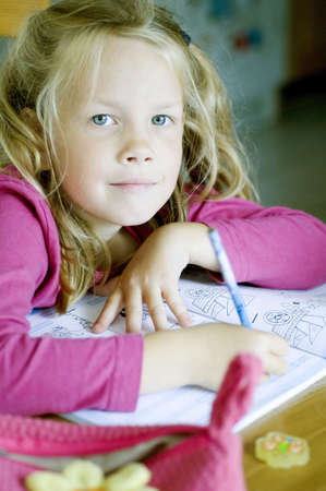 Girl smiling at camera while doing her homework Stock Photo - 3193864
