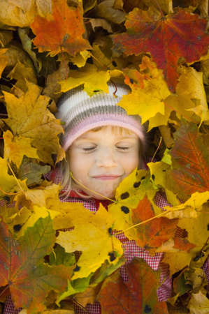 autumn colour: Girl with autumn leaves covering her
