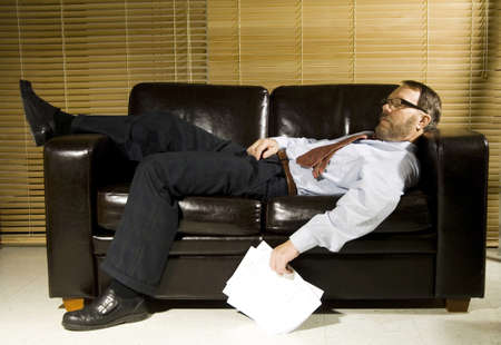 couch: Exhausted businessman sleeping on the couch