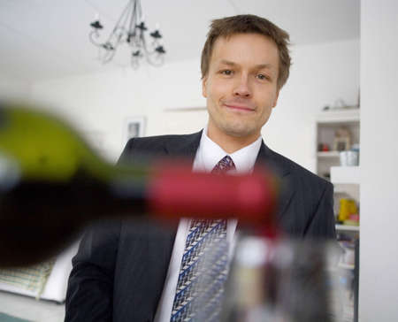 Blurrred wine bottle and glass with a businessman in the background