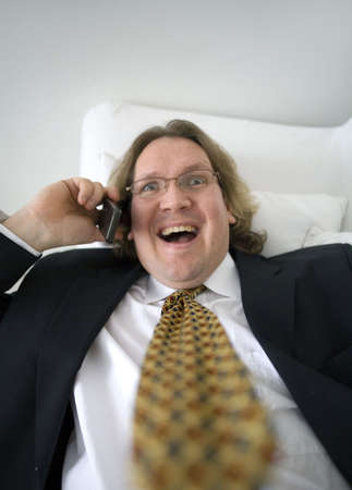 Businessman talking happily on the phone while lying on the couch