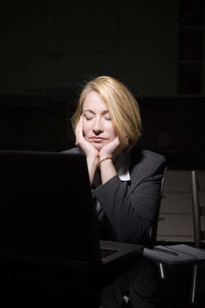 computering: Businesswoman resting her eyes after staring too long at the laptop