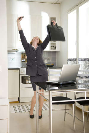 computering: Businesswoman dancing with joy in the kitchen