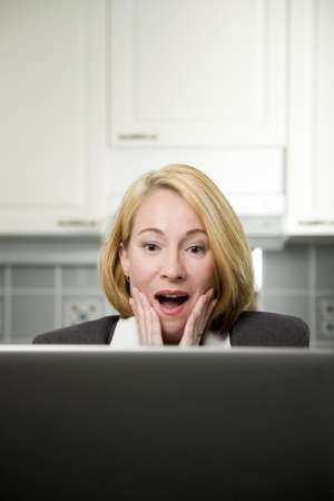 computering: Businesswoman surprised by information shown on her laptop LANG_EVOIMAGES