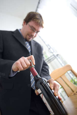 Businessman opening a bottle of wine LANG_EVOIMAGES