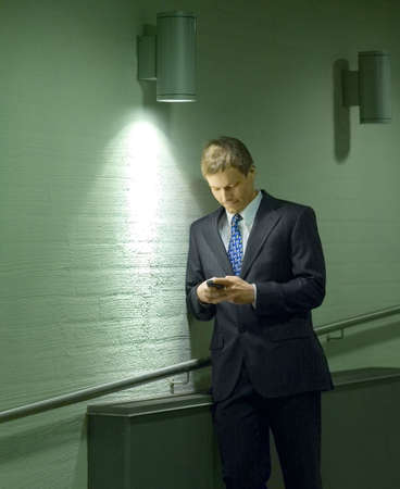 Businessman text messaging on the mobile phone LANG_EVOIMAGES