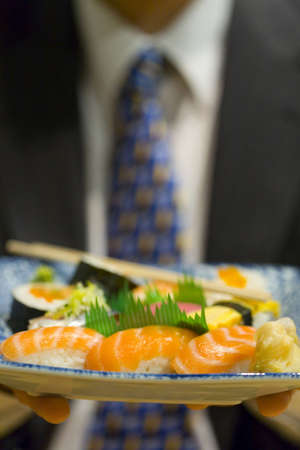 Businessman holding a plate of sushi LANG_EVOIMAGES