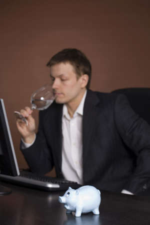 Businessman drinking water in the office with piggy bank on focus LANG_EVOIMAGES