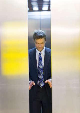people in elevator: Businessman opening the elevator doors LANG_EVOIMAGES