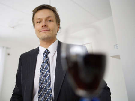 Blurrred wine glass with businessman in the background