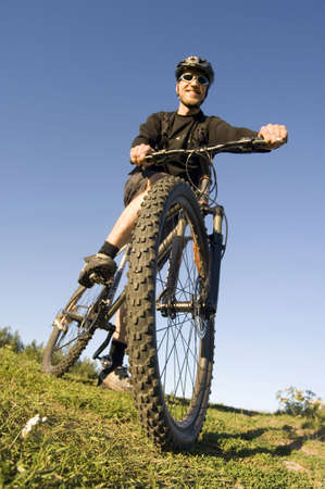 Man sitting on the bicycle smiling at the camera Stock Photo - 3193987