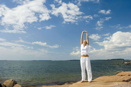 Woman practising yoga by the seaside LANG_EVOIMAGES