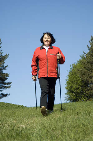 Senior woman strolling with walking sticks outdoors Stock Photo - 3193997
