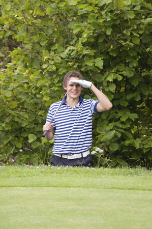Man shielding his eyes while holding golf club