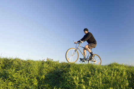 Man lifting the front wheel of bicycle while riding on it LANG_EVOIMAGES