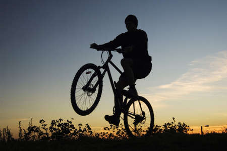 road bike: Silhouette of man lifting the front wheel of bicycle while riding on it