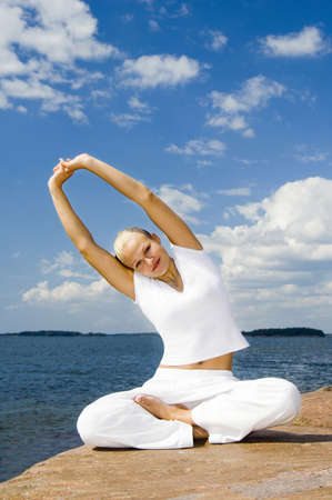Woman smiling at the camera while practising yoga LANG_EVOIMAGES