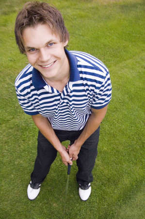 Man smiling at the camera while playing golf LANG_EVOIMAGES