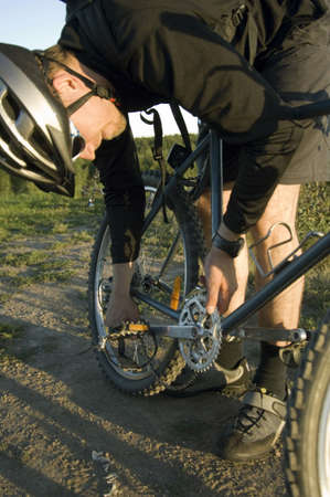 road bike: Man fixing bicycle chain