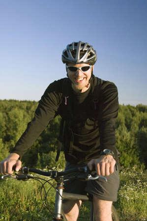 Man smiling while riding on bicycle