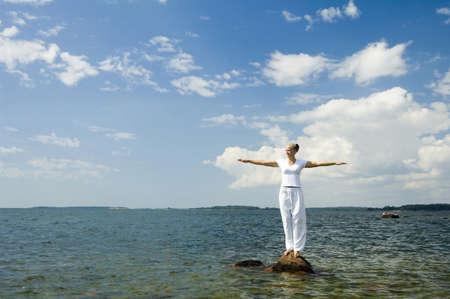 calmness: Woman standing on rock spreading her hands LANG_EVOIMAGES